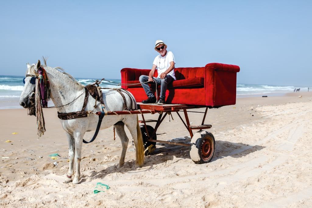 Horst Wackerbarth auf der roten Couch in Westafrika (Foto: George Sylva)