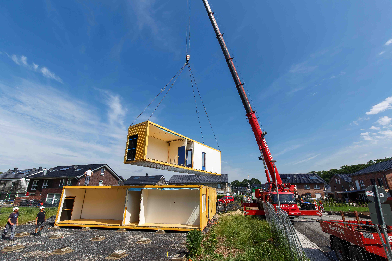 Ein Autokran hievt die Pavillons an ihren Standort an den Holunderweg. Dort finden zwei Kita-Gruppen Platz, ehe es ab 2021 in den Neubau in Sprakel-Ost geht. (Foto: Presseamt Münster)