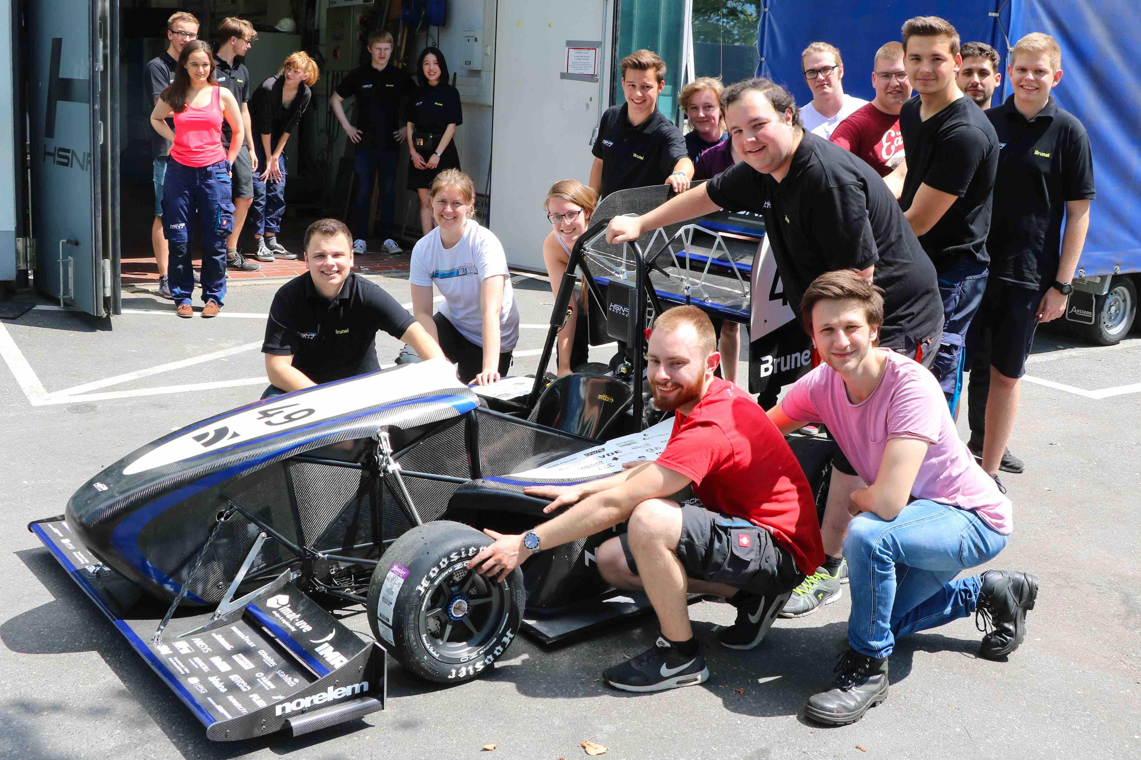 Der neue Rennwagen mit Teilen des Teams vor der Werkstatt. (Foto: Hochschule Niederrhein)