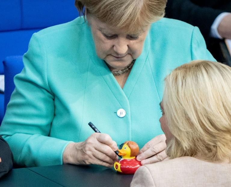 """Merkel signiert im Bundestag """"Badeente Angie"""" für Klöckner (© 2019 AFP)"""