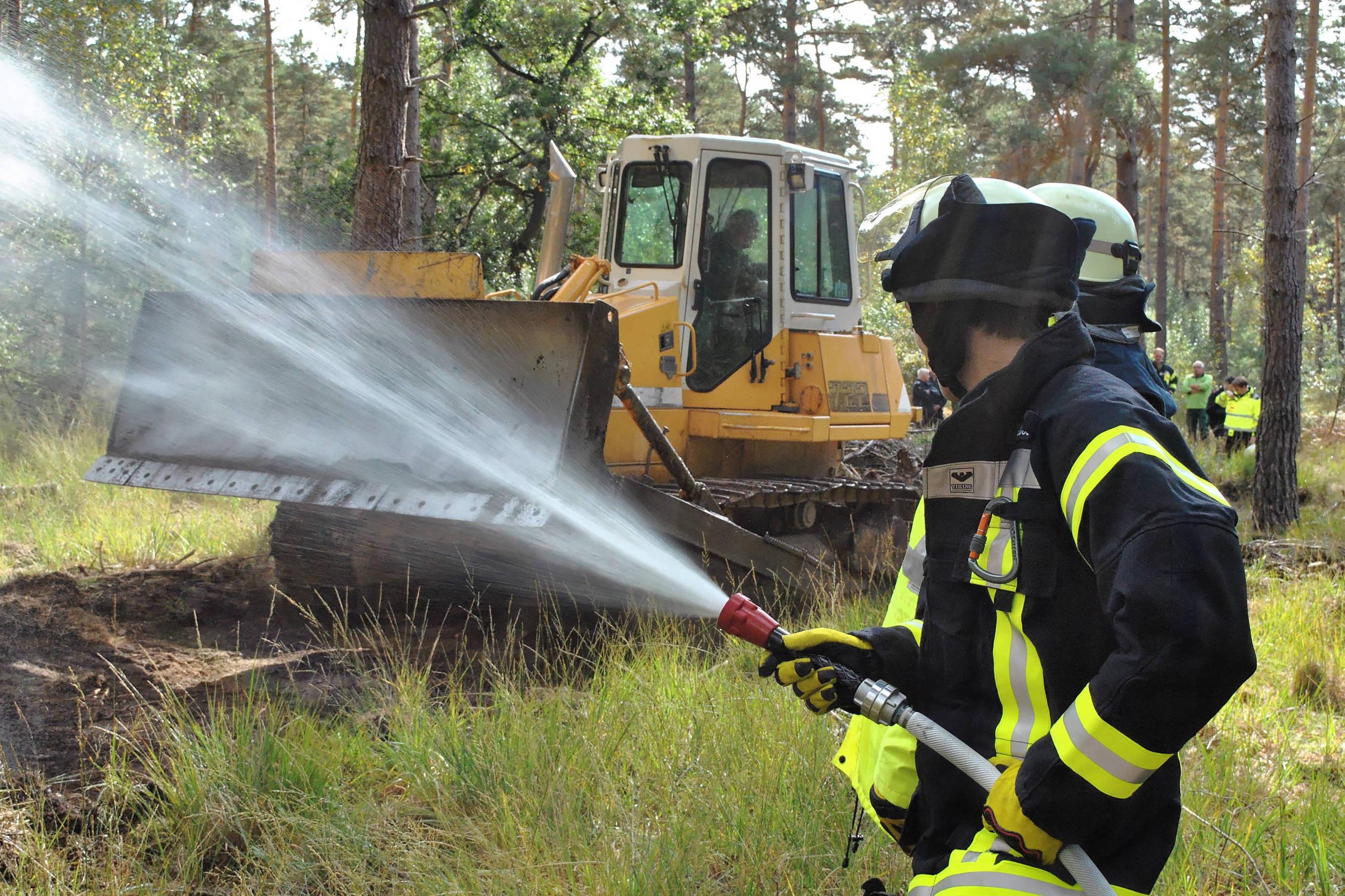 Ein Bulldozer schiebt eine Schneise durch das Unterholz. Um ein Übertreten des Brandes zu verhindern, wird die Schneise gewässert. (Foto: Kreis Viersen)
