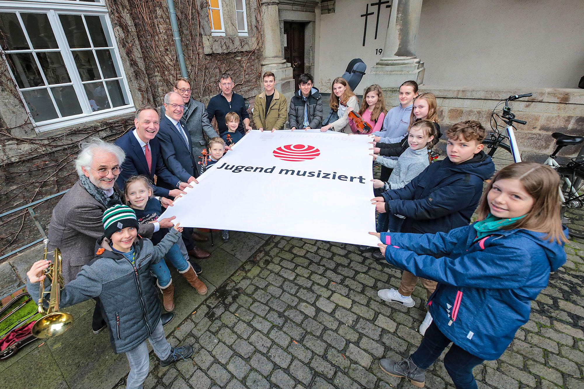 Jugend musiziert – Schülerinnen und Schüler, die Musikschulleiter, Oberbürgermeister Reiners und die Sponsoren der Sparkasse und Piano Kalscheuer sind gespannt auf den Wettbewerb. (Foto: Stadt MG)