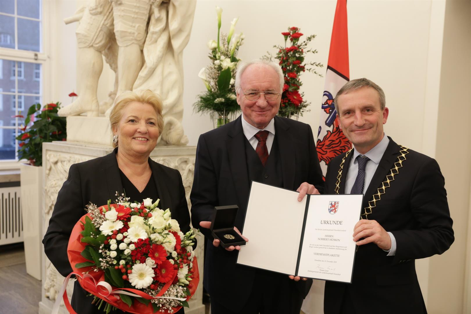 OB Thomas Geisel überreichte Norbert Hüsson die Verdienstplakette. Mit im Bild Ehefrau Dr. Andrea Hüsson (Foto: Stadt Düsseldorf/Ingo Lammert)