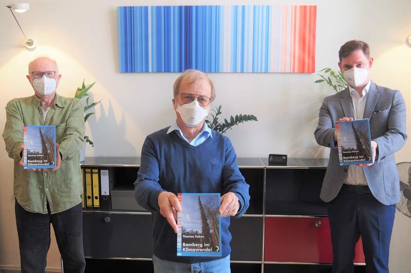 """Verleger Erich Weiß, Autor Thomas Foken und Klimareferent Jonas Glüsenkamp vor der """"Bamberger Reihe"""". (Foto: Anna Lienhardt)"""