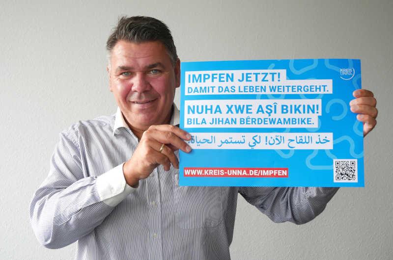 Landrat Mario Löhr zeigt eines der Motive der mehrsprachigen Impfkampagne. (Foto: Birgit Kalle)