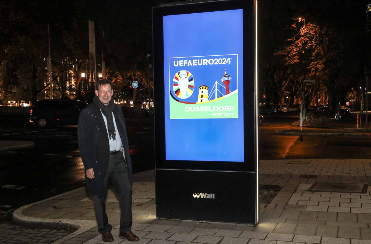 Stadtdirektor Burkhard Hintzsche an einem der 44 digitalen Werbeträger mit dem UEFA Euro2024 Düsseldorf-Logo (Foto: Melanie Zanin/Stadt Düsseldorf)